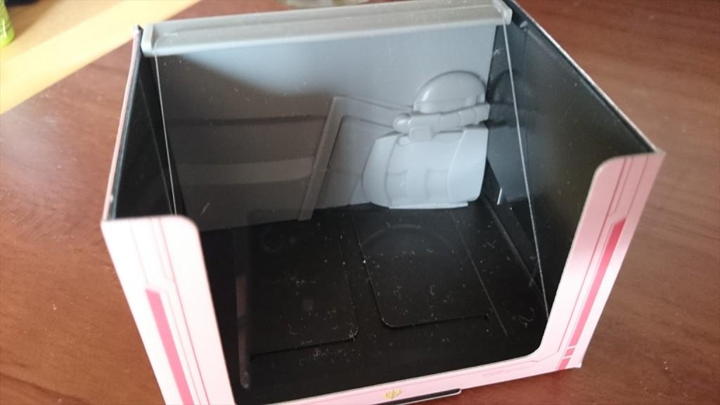 紙の箱の中にザク型のプラスチックでできた背景と、透明なプラスチック板を斜めにセットする